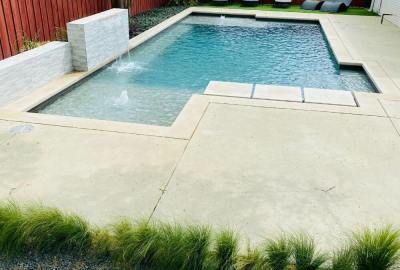 Formal pool with tanning ledge and water features