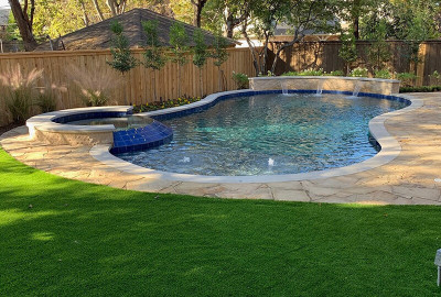 Freeform pool with raised spa and raised wall with scuppers