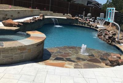 Freeform pool with raised spa wall and rocks