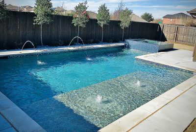 Geometric pool with tanning ledge bubblers deck jets